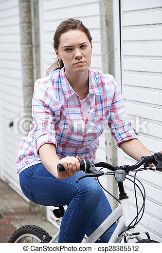 Portrait Of Unhappy Teenage Girl In Urban Setting Riding Bike - csp28385512