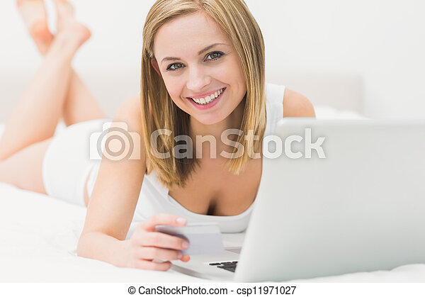 Portrait of woman doing online shopping in bed  - csp11971027