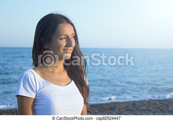 Portrait of woman dressed in white on the beach - csp82524447