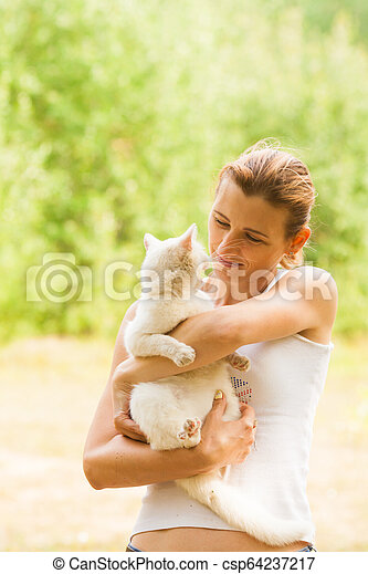 Portrait of woman looking into cat's eyes - csp64237217