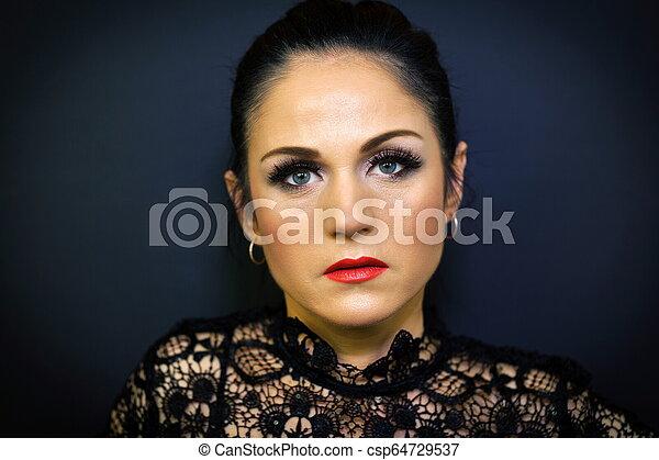 Portrait of woman on dark background - csp64729537