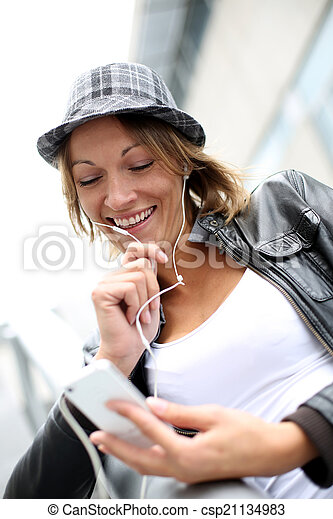 Portrait of woman using smartphone in town - csp21134983
