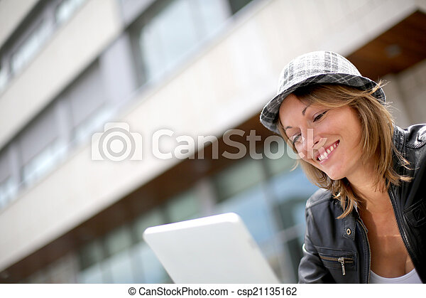 Portrait of woman using tablet in town - csp21135162