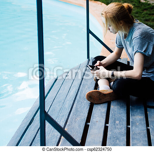 Portrait of Young Beautiful Smiling Blonde Girl Using Smartphone while Sitting on the Bridge. - csp62324750