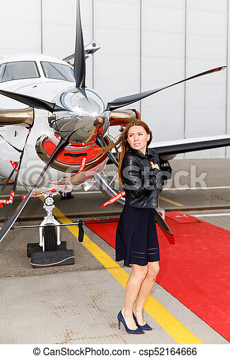 portrait of young beautiful woman near a chrome fairing of a propeller of the business jet - csp52164666