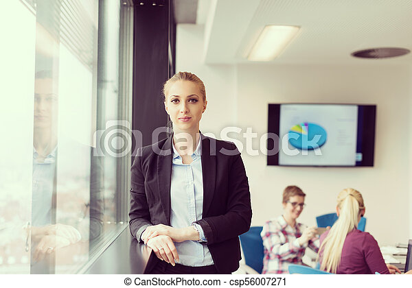 portrait of young business woman at office with team on meeting in background - csp56007271