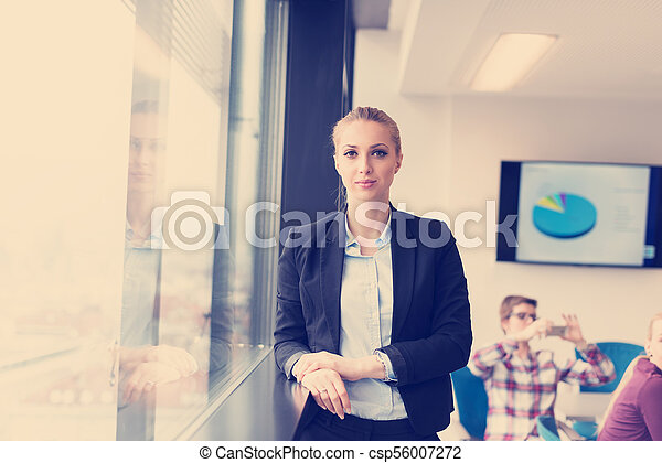 portrait of young business woman at office with team on meeting in background - csp56007272