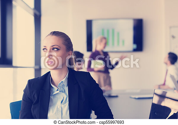portrait of young business woman at office with team on meeting in background - csp55997693