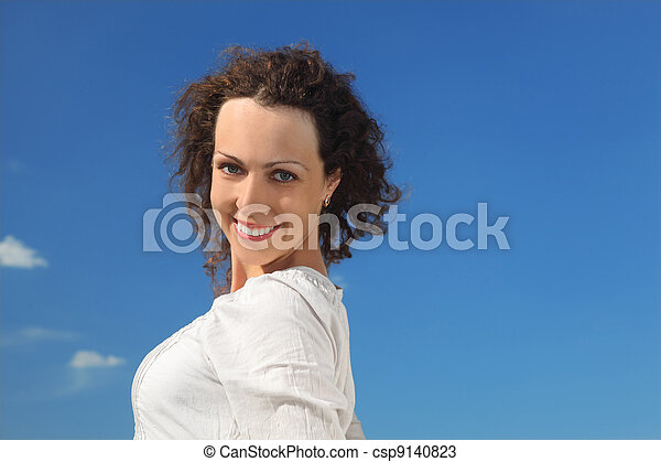 portrait of young curl woman smiling, blue sky - csp9140823
