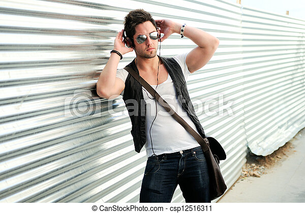 Portrait of young happy man in urban background - csp12516311