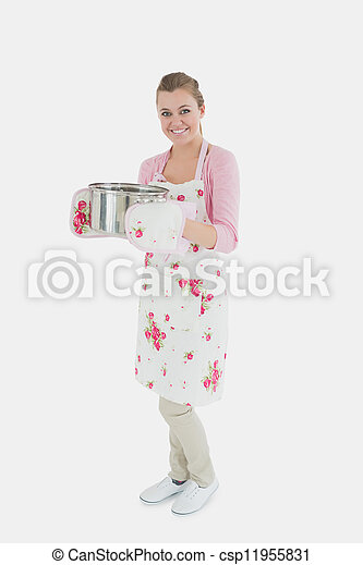 Portrait of young maid in apron holding utensil - csp11955831