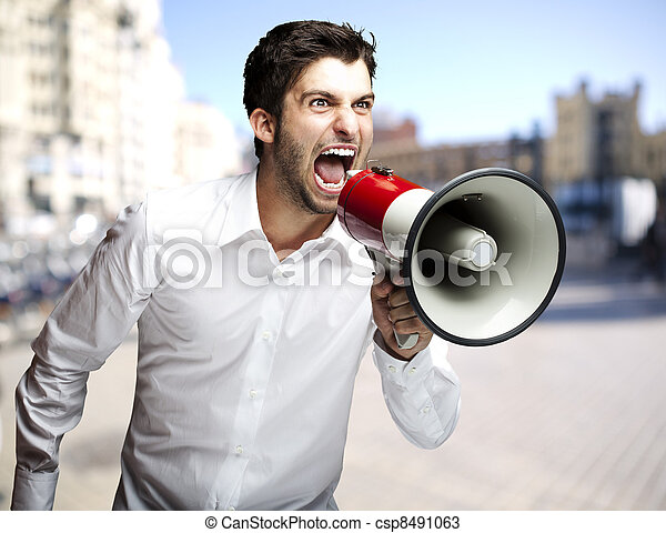 portrait of young man screaming with megaphone at city - csp8491063