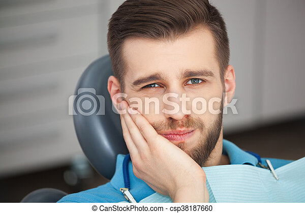 Portrait of young man with tooth pain sitting in a dentist's chair. - csp38187660
