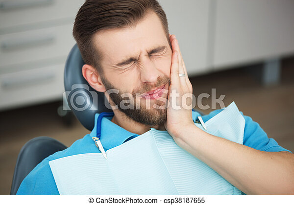 Portrait of young man with tooth pain sitting in a dentist's chair. - csp38187655