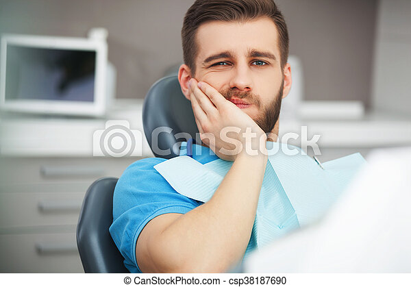 Portrait of young man with tooth pain sitting in a dentist's chair. - csp38187690