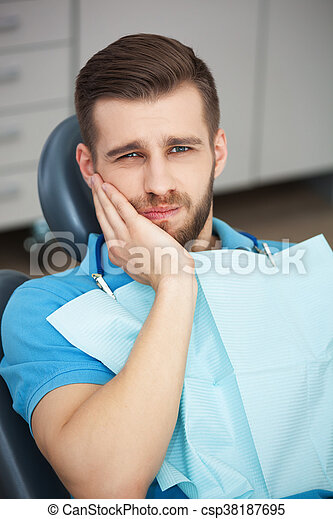 Portrait of young man with tooth pain sitting in a dentist's chair. - csp38187695