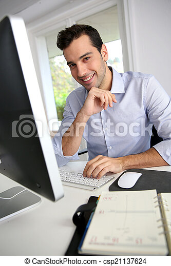 Portrait of young office worker sitting at desk - csp21137624