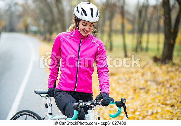 Portrait of Young Smiling Female Cyclist in Pink Jacket Resting with Road Bicycle in the Cold Sunny Autumn Day - csp61027480