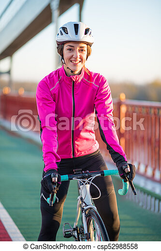 Portrait of Young Smiling Female Cyclist in Pink Jacket Resting with Road Bicycle in the Cold Sunny Autumn Day - csp52988558