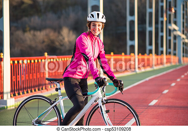 Portrait of Young Smiling Female Cyclist in Pink Jacket Resting with Road Bicycle in the Cold Sunny Autumn Day - csp53109208