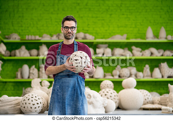 Portrait of Young SmilingCeramist in the Bright Modern Ceramic Workshop Holding Sculpture. Small Business Concept. - csp56215342
