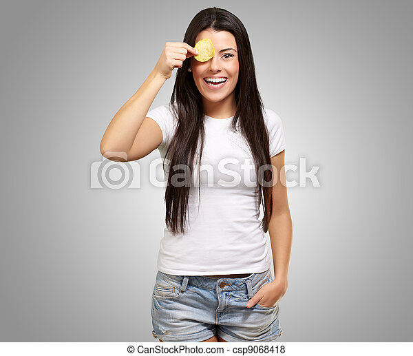 portrait of young woman holding a potato chip in front of her eye over grey - csp9068418