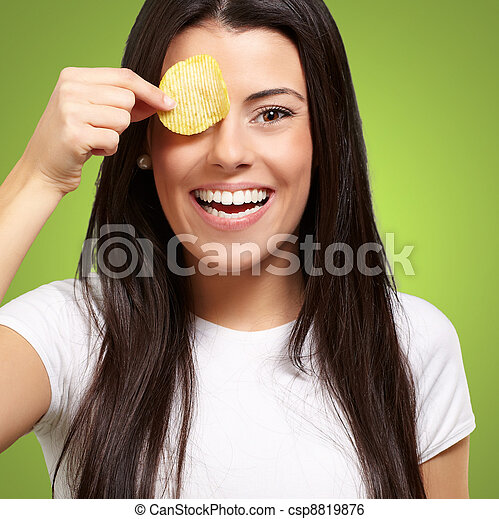 portrait of young woman holding a potato chip in front of her eye over green - csp8819876