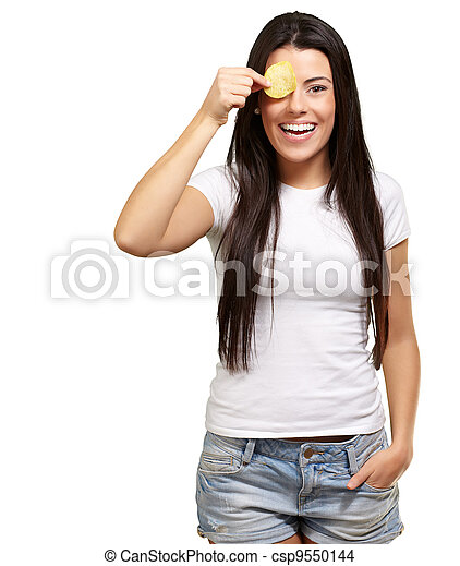 portrait of young woman holding a potato chip in front of her eye over white - csp9550144