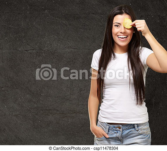 portrait of young woman holding a potato chip in front of her eye against a grunge wall - csp11478304