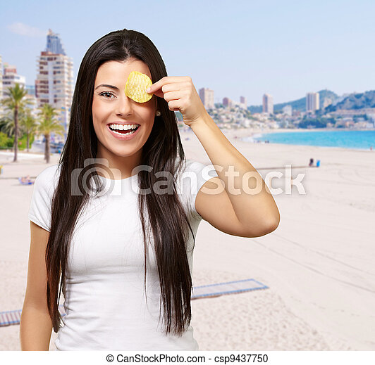 portrait of young woman holding potato chip in front of her eye against a coastline - csp9437750