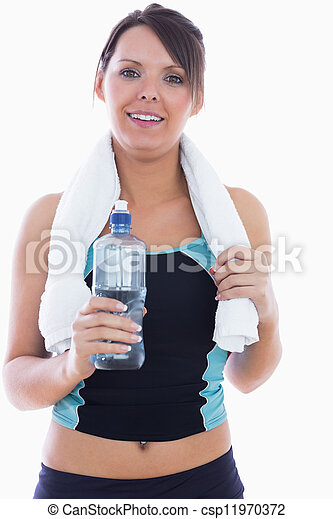 Portrait of young woman in sportswear holding towel around neck and water bottle over white background - csp11970372