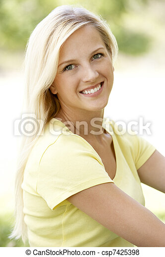 Portrait Of Young Woman Sitting In Park - csp7425398