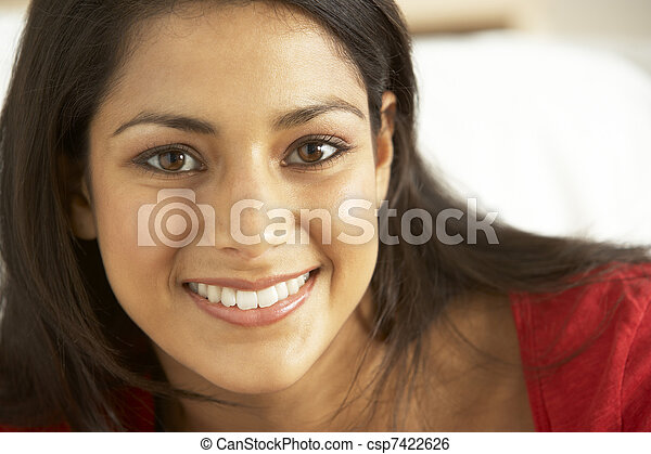 Portrait of young woman sitting on sofa - csp7422626