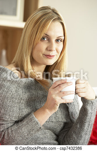 Portrait Of Young Woman Sitting On Sofa With Cup Of Coffee - csp7432386