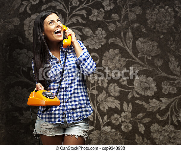 portrait of young woman talking on vintage telephone against a vintage wall - csp9343938