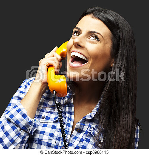 portrait of young woman talking on vintage telephone over black - csp8968115