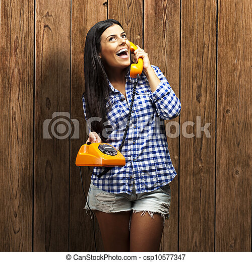 portrait of young woman talking on vintage telephone against a wooden wall - csp10577347