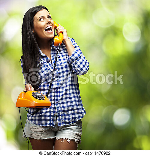 portrait of young woman talking on vintage telephone against a nature background - csp11476922