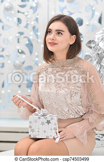 Portrait of young woman with present box - csp74503499