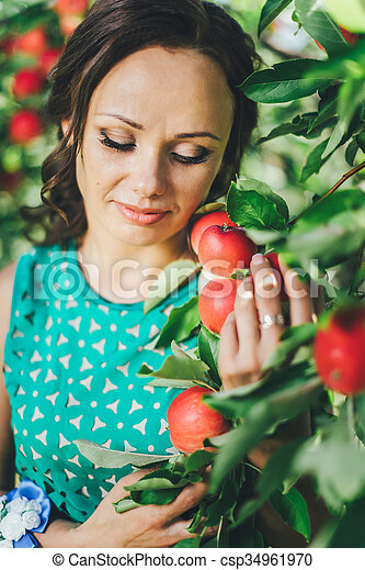 portrait of young woman with red apple in garden - csp34961970