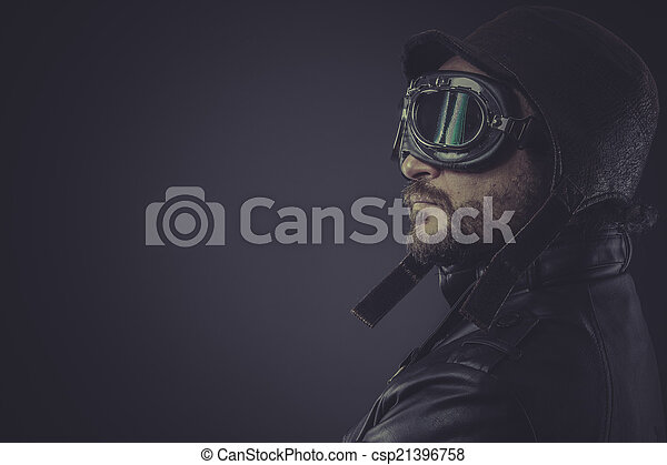 portrait pilot dressed in vintage style leather cap and goggles - csp21396758