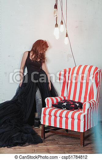 Retrato largo de joven y hermosa mujer parada cerca de un sillón antiguo - csp51784812