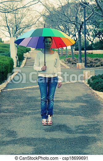 Una joven parada bajo un gran paraguas arcoíris - csp18699691