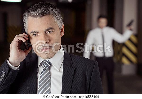 Asesino y víctima. Hombre de negocios seguros y maduros hablando por teléfono móvil mientras otros hombres armados están detrás de él - csp16556194
