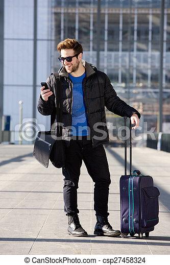 Un hombre feliz de pie en la estación con bolsa y teléfono móvil - csp27458324