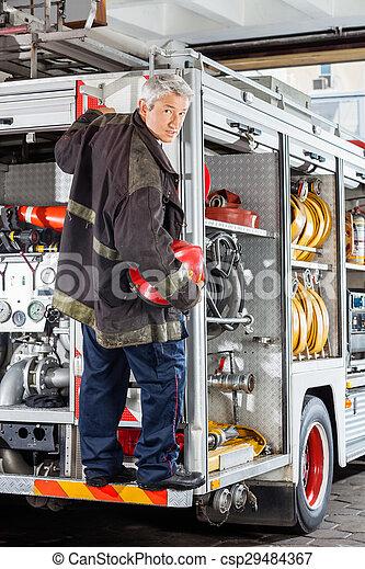Bombero confiado parado en un camión en la estación de bomberos - csp29484367