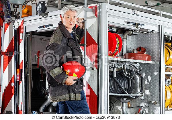 Bombero confiado parado en el motor de fuego - csp30913878