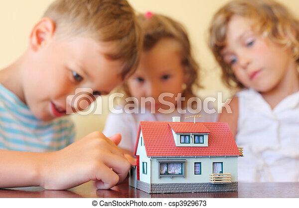 Los niños tres juntos mirando el modelo de casa de pie sobre la mesa en el cuarto acogedor, enfocado en la casa - csp3929673