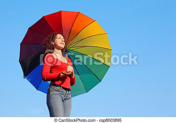 La chica está de pie contra el cielo azul, sosteniendo sombrilla sobre el color y mira al sol - csp8003895
