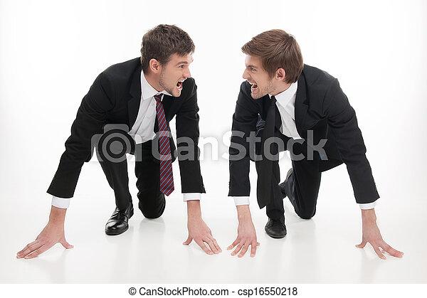 Competencia de negocios. Dos jóvenes empresarios enojados parados en la línea de salida y mirándose unos a otros mientras están aislados en blanco - csp16550218